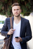 Young businessman walking outside with mobile phone and bag Stock Photos