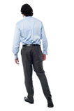 Young businessman in walking posture Stock Images
