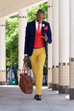 Young businessman walking and reading text message on cell phone. Full length portrait of young african businessman walking and reading text message on cell Stock Photo