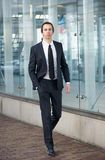 Young businessman walking on sidewalk in a suit Royalty Free Stock Images