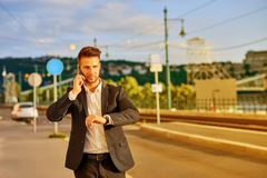 Young businessman walking on the street and talking on a phone Stock Photo