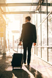 Young businessman walking with suitcase outside airport building Royalty Free Stock Photos
