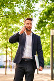 Young businessman walking on the sunny street and talking on a p Stock Images