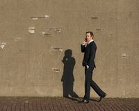 Young businessman walking and talking on mobile phone Royalty Free Stock Image