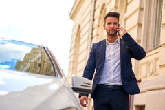 Young businessman walking to his car and talking on a phone Royalty Free Stock Images