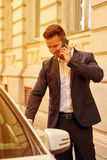 Young businessman walking to his car and talking on a phone Stock Photography