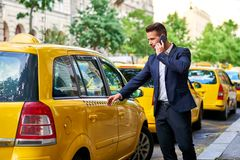 Young businessman walking to a taxi and talking on a phone royalty free stock image