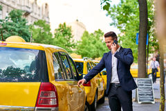 Young businessman walking to a taxi and talking on a phone Stock Image