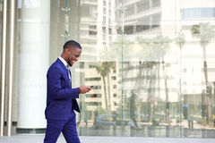 Young businessman walking and using cell phone Royalty Free Stock Photos