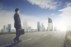Young businessman walks toward to modern city royalty free stock photography