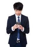 Young businessman was writing a message with a phone. Isolated on white background Royalty Free Stock Images