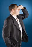 Young businessman watching - hand at his forehead Royalty Free Stock Images
