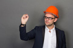Young businessman wear a safety helmet, writing Royalty Free Stock Photography