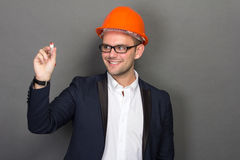 Young businessman wear a safety helmet, writing Royalty Free Stock Photos