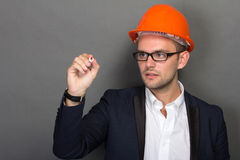 Young businessman wear a safety helmet, writing Stock Photos