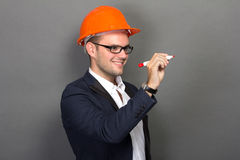 Young businessman wear a safety helmet, writing Royalty Free Stock Photo
