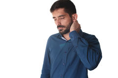 Young businessman wearing blue shirt holding his neck on white b Stock Photography