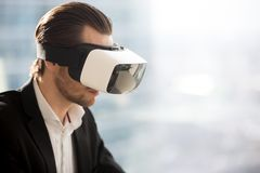 Young businessman wearing futuristic virtual reality glasses. Stock Photos