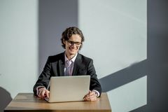 Businessman wearing glasses working with laptop at office. Young businessman wearing glasses working with laptop at office Royalty Free Stock Image