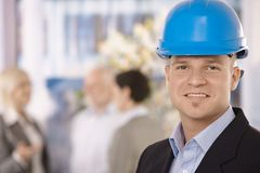 Young businessman wearing hardhat. Designer coworkers talking in office background Stock Images