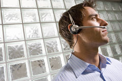 Young businessman wearing headset by glass block wall, low angle view (tilt) Stock Images