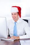 Young Businessman Wearing Santa Hat Using Computer In Office Royalty Free Stock Photography