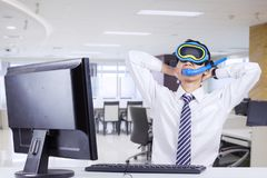 Young businessman imagining his vacation. Young businessman wearing snorkeling equipment while imagining his vacation and sitting in the office Royalty Free Stock Images