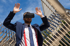 Young businessman wearing virtual reality glasses and doing gest. Ures outdoors Stock Image