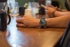 Businessman wearing wrist watch on his arm. while staying in mee. Young businessman wearing wrist watch on his arm. while staying in meeting room have ceramic Royalty Free Stock Images