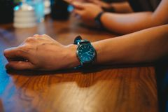 Businessman wearing wrist watch on his arm. while staying in mee. Young businessman wearing wrist watch on his arm. while staying in meeting room have ceramic Stock Photos