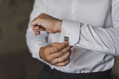 Young businessman wears cufflinks on the lapels of his shirt 547. The man pulls out a box of cuff links Royalty Free Stock Photography