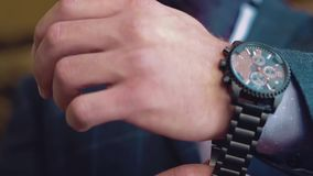 Young businessman wears a wristwatch stock footage