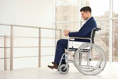 Young businessman in wheelchair using tablet. Near window indoors royalty free stock image