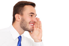 Young businessman whispering over white background Royalty Free Stock Image