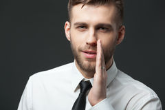 Young businessman whispering trade secrets on dark gray backgro Stock Photography