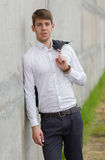 Young businessman in white shirt leaning on wall. Outside Stock Photos