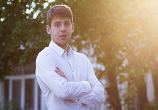 Young businessman in white shirt outside. Confident young businessman in white shirt outdoors at sunset arms crossed royalty free stock photography