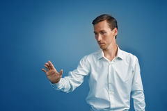Young businessman in white shirt working with the invisible screen or virtual holographic interface. Stock Images