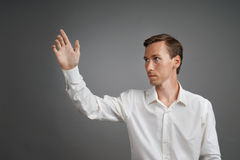 Young businessman in white shirt working with the invisible screen or virtual holographic interface. Royalty Free Stock Photos