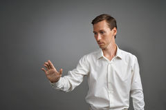 Young businessman in white shirt working with the invisible screen or virtual holographic interface. Stock Photos