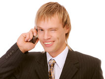 Young businessman winks and speaks by phone Royalty Free Stock Photography