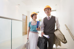 Young businessman and woman in hard hats in office, woman looking at man, low angle view, Stock Photo