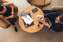 Young businessman and woman meeting in office lobby. Overhead view of young businessman and women meeting in office lobby. Coworkers discussing new business Royalty Free Stock Photos