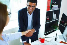 Young businessman and woman shaking hands in office Royalty Free Stock Photo