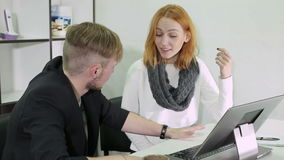 Young businessman and woman talking with different emotions. Two people have a conversation in the office sitting at the table stock footage