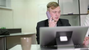 Young businessman and woman working in the office. Man talking by phone stock video