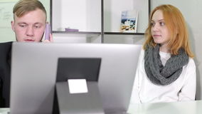 Young businessman and woman working in the office. They sit at the table. On the table is a laptop stock footage