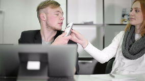 Young businessman and woman working in the office. Woman talking by phone. Lady is answering the phone call and handing the phone to the man stock video footage