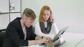 Young businessman and woman working in the office. Woman is talking on phone. Man is tapping on a laptop keyboard and writing some notices on a paper stock footage