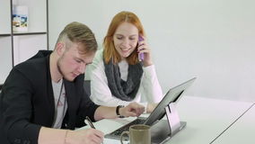 Young businessman and woman working in the office. Woman is talking on phone. Man is tapping on a laptop keyboard and writing some notices on a paper stock video footage